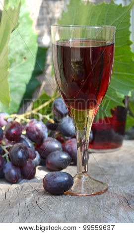 A glass of red wine and blue grapes