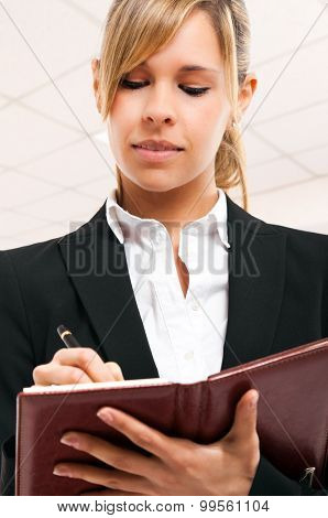Smiling business woman writing on her agenda