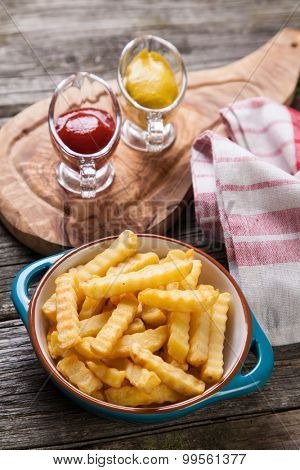 Bowl of french fries on old wood background