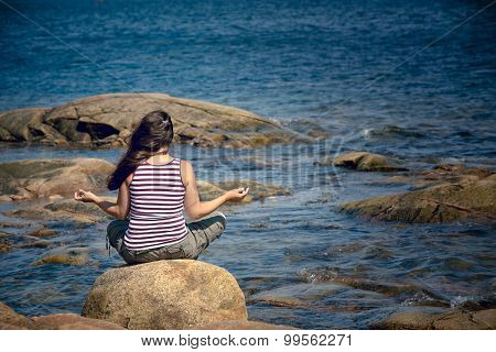 Young woman meditates while sitting on rock by the sea,