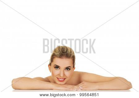 Young beautiful woman based on table, isolated on white.