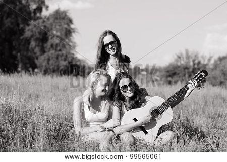 Three young people teenage girls playing guitar