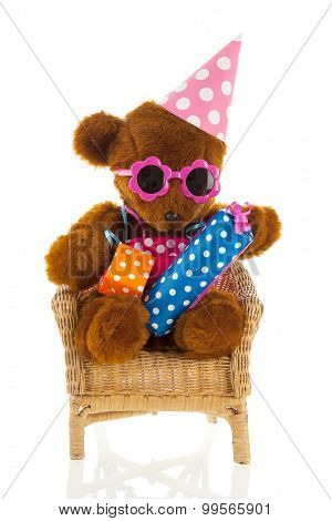 Funny stuffed bear with colorful birthday gifts isolated over white background