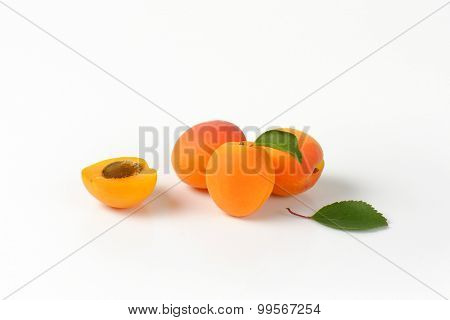 whole and halved apricots with leaves