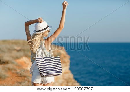 The girl looks at the sea, standing on a rock