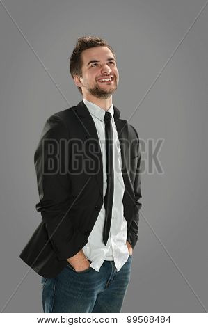 Portrait of young businessman smiling in casual clothing over gray background