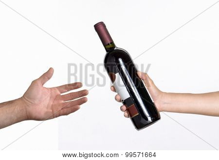 Hand giving red wine bottle.