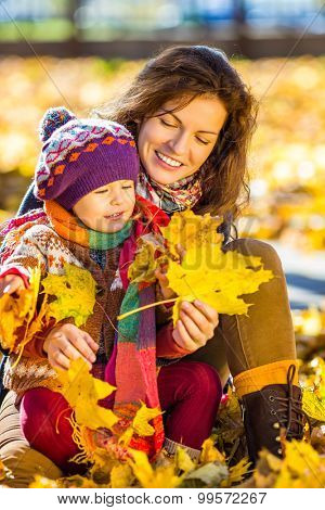 Little girl and her mother playing in the autumn park