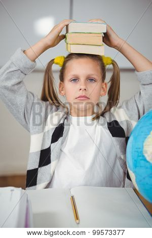 Portrait of cute pupil balancing books on head in a classroom in school