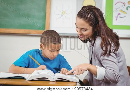 Pretty teacher helping pupil at his desk in a classroom