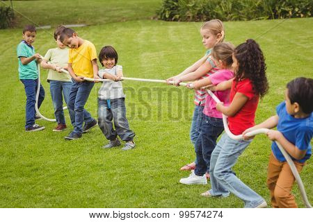 Cute pupils playing tug of war on the grass outside on elementary school campus
