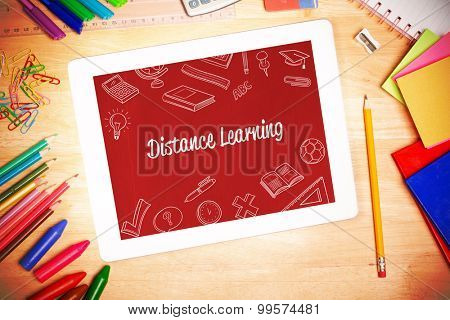 The word distance learning and school doodles against students desk with tablet pc