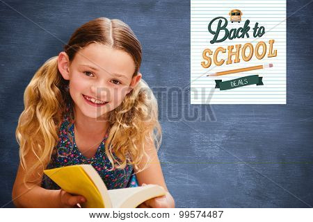 Cute little girl reading book in library against blue chalkboard