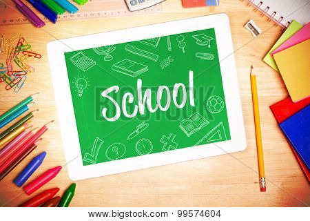 The word school and school doodles against students desk with tablet pc