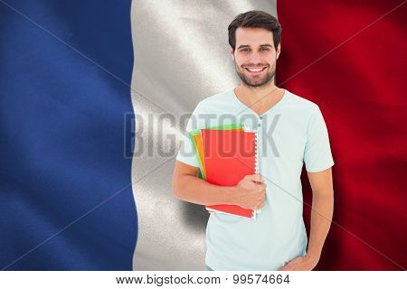 Student holding notepad against digitally generated france national flag