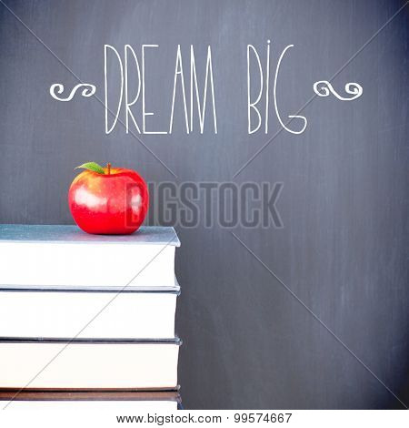The word dream big against red apple in front of blackboard on books
