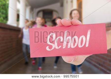 The word school and hand showing card against cute pupils running down the hall