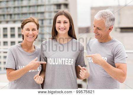 Portrait of smiling volunteers pointing on shirt on roof of building