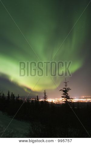 Active Aurora Borealis In The Sky Over Town Lights