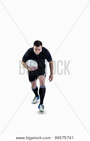 Determined rugby player running with the rugby ball