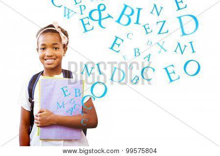 Little girl holding folders in school corridor against letters