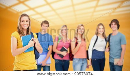 A group of college students standing as one girl stands in front of them against white room with windows at ceiling