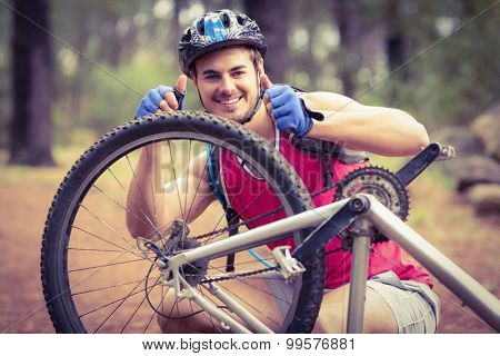 Happy handsome biker repairing bike showing thumbs up in the nature
