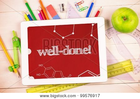 The word well-done! and science graphic against students desk with tablet pc