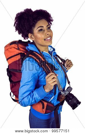 A young woman with camera and backpack against a white background