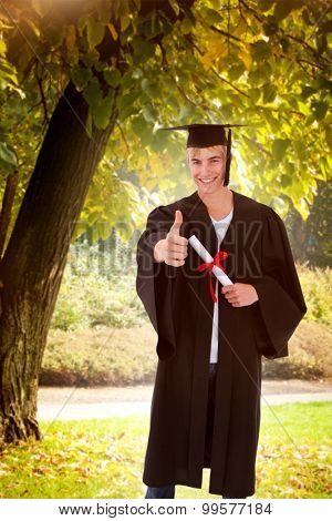 Happy Teen Guy Celebrating Graduation against trees and meadow in the park
