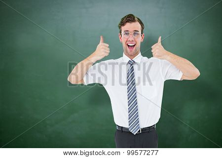Happy geeky businessman with thumbs up against green chalkboard