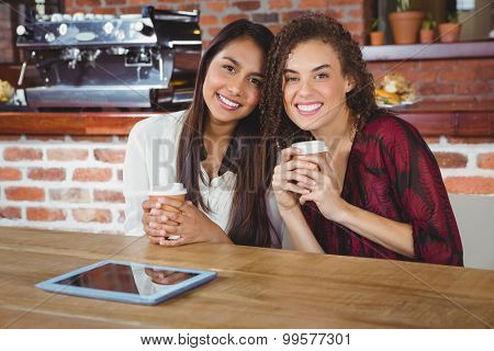 Pretty female friends enjoying a coffee using tablet pc at the coffee shop