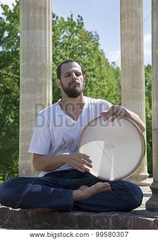 Young Man Playing The Tambourine Outdoors