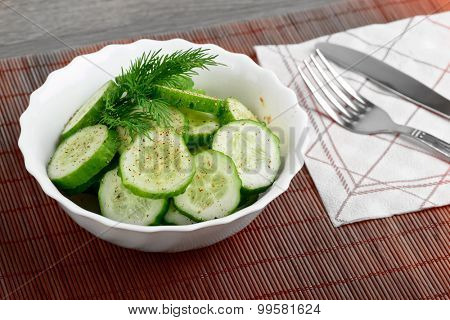 Fresh cucumber salad in bowl on wooden board