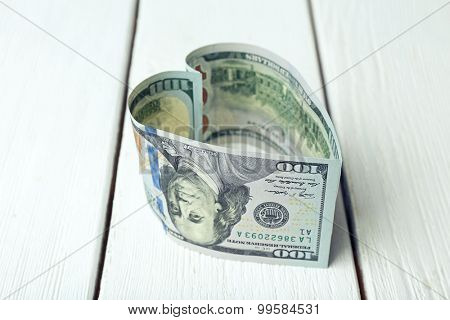 Dollars folded into heart on wooden background