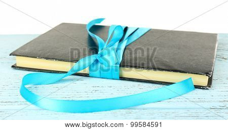 Book wrapped with color ribbon on table isolated on white