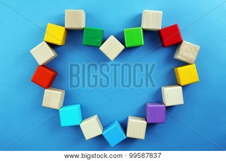 Colorful cubes in heart shape on blue background
