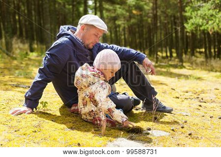 parent teaching child on forest background