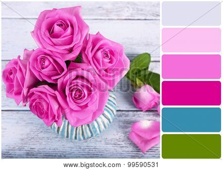 Beautiful pink roses on wooden background and palette of colors