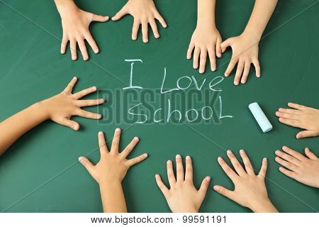 Children hands on blackboard background