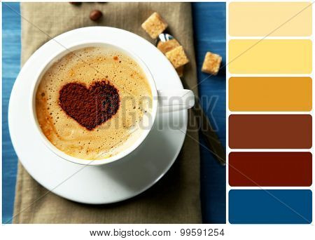 Cup of cappuccino with heart of cocoa on wooden table and palette of colors