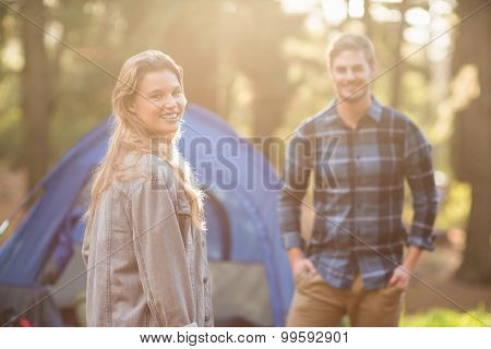 Happy young camper couple smiling at the camera in the nature