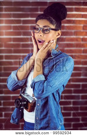 Portrait of a hipster surprised with her camera against a brick wall