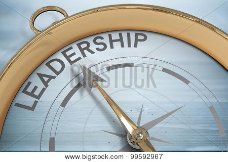 Compass pointing to leadership against bleached wooden planks background