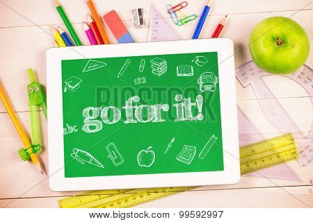 The word go for it! and education doodles against students desk with tablet pc
