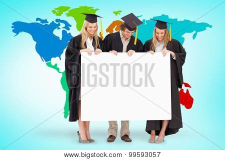 Three smiling students in graduate robe holding a blank sign against blue vignette background