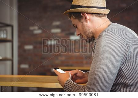 Handsome hipster sitting and texting at coffee shop