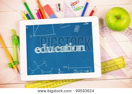 The word education and math and science doodles against students desk with tablet pc