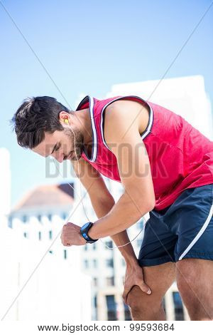 Exhausted athlete looking at his stopwatch on a sunny day