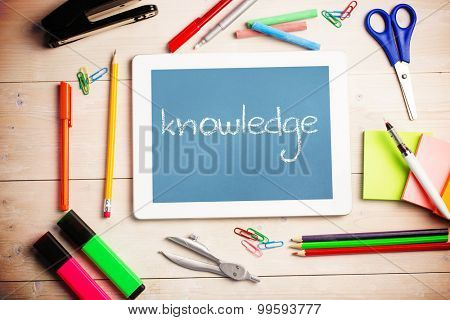 The word knowledge and students desk with tablet pc against blue
